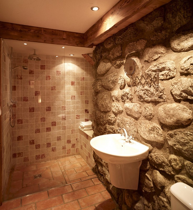 Bathroom with walk in shower and exposed granite wall